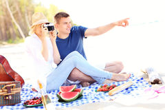 Young couple taking pictures at the beach Stock Image
