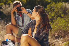Young couple taking pictures on hiking trip Stock Photo