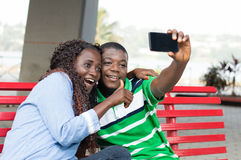 Young couple taking pictures with their mobile phone. Stock Photo
