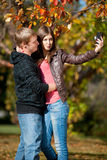 Young couple taking pictures of themselves in park Royalty Free Stock Photo