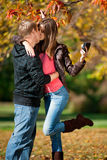 Young couple taking pictures of themselves in park Royalty Free Stock Photography