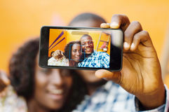 Young couple taking pictures throught mobile phone. Royalty Free Stock Image