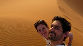 A young couple taking a self picture while climbing to the top of the Great Sand Dune in the red dune sea of Erg Chebbi, Morocco Stock Photos