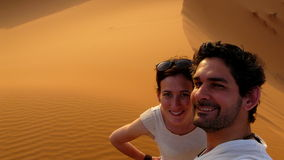 A young couple taking a self picture while climbing to the top of the Great Sand Dune in the red dune sea of Erg Chebbi, Morocco Royalty Free Stock Photo