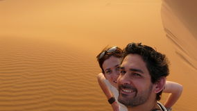 A young couple taking a self picture while climbing to the top of the Great Sand Dune in the red dune sea of Erg Chebbi, Morocco Stock Photo
