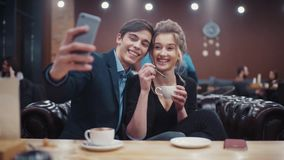 Young couple taking self-portrait photo kissing, laughing and enjoying each other having a date in an urban café. Young couple taking self-portrait photo stock video footage