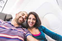 Young couple taking a selfie on the airplane Stock Photography