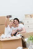 Young couple taking a selfie as they unpack Stock Image