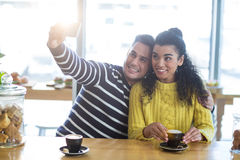 Young couple taking selfie in cafeteria Royalty Free Stock Photos