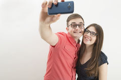 Young couple taking a selfie with a cell phone  on white Royalty Free Stock Photos