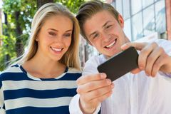Young couple taking a selfie. In city royalty free stock image