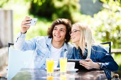Young couple taking selfie while drinking coffee at cafe`s garde. N Stock Photography