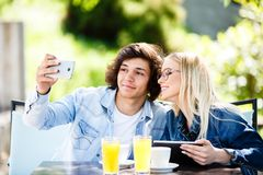Young couple taking selfie while drinking coffee at cafe`s garde. N Royalty Free Stock Images