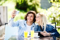 Young couple taking selfie while drinking coffee at cafe`s garde. N Stock Images
