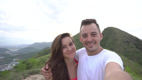 Young couple taking selfie, laughing and go round in the mountains with beautiful aerial city view at sunset, enjoy the stock video footage