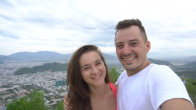 Young couple taking selfie,laughing and go round in the mountains with city view. Young couple taking selfie, laughing and go round in the mountains with stock video footage
