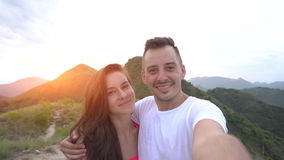 Young couple taking selfie, laughing in the mountains. At sunset, enjoy the nature and carefree life Royalty Free Stock Photos