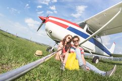 Young couple taking selfie at private airplane travel trip. Young couple taking selfie at lightweight airplane - Happy people boarding on excursion air plane Royalty Free Stock Image