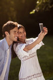 Young couple taking a selfie in the park. Beautiful young couple taking a selfie in a park in summer Royalty Free Stock Photography