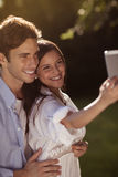 Young couple taking a selfie in the park. Beautiful young couple taking a selfie in a park in summer Royalty Free Stock Photo
