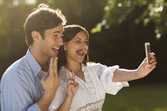 Young couple taking a selfie in the park. Beautiful young couple taking a selfie in a park in summer Stock Photo