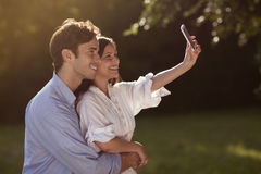 Young couple taking a selfie in the park. Beautiful young couple taking a selfie in a park in summer Royalty Free Stock Image