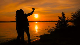 Young couple taking selfie photo on beach during sunset, super slow motion. On orange background stock video footage
