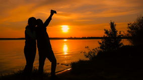 Young couple taking selfie photo on beach during sunset, super slow motion stock video footage