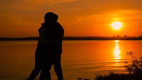 Young couple taking selfie photo on beach during sunset, super slow motion. On orange background stock video