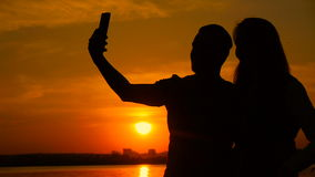 Young couple taking selfie photo on beach during sunset, super slow motion. On orange background stock footage
