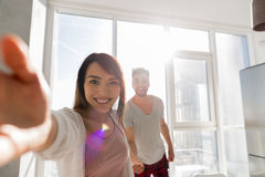 Young Couple Taking Selfie Photo Holding Hands In Kitchen, Asian Woman Leading Hispanic Man. Modern Apartment With Big Windows Interior stock image