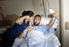 Young couple taking selfie photo at hospital room with man lying in clinic bed. Young happy couple in love taking selfie photo at hospital room with men ill Stock Images
