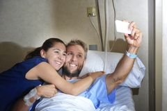Young couple taking selfie photo at hospital room with man lying in clinic bed. Young happy couple in love taking selfie photo at hospital room with men ill Royalty Free Stock Photography