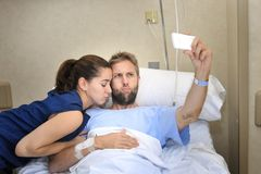 Young couple taking selfie photo at hospital room with man lying in clinic bed. Young happy couple in love taking selfie photo at hospital room with men ill Stock Photography