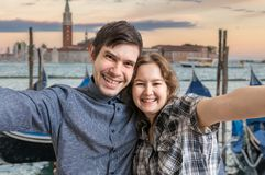 Young couple is taking selfie photo in Venice in Italy. Gondolas in background royalty free stock photography