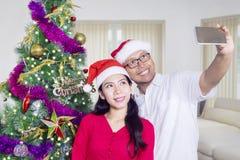 Couple with Christmas tree taking selfie photo Stock Photo