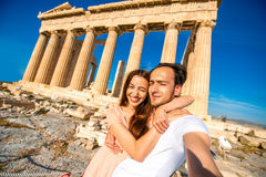 Young couple taking selfie picture with Parthenon temple on background in Acropolis Royalty Free Stock Image