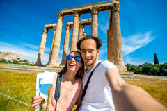Young couple taking selfie picture with Zeus temple on background in Acropolis Royalty Free Stock Images
