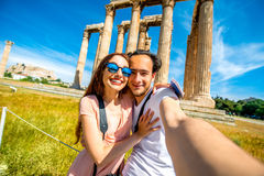 Young couple taking selfie picture with Zeus temple on background in Acropolis Stock Photography