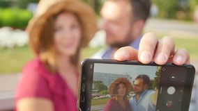 Young couple taking a selfie portrait while relaxing in a city park. Happy lovers want to capture a pleasant moment stock video footage