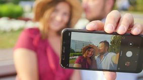Young couple taking a selfie portrait while relaxing in a city park. Happy lovers want to capture a pleasant moment stock footage