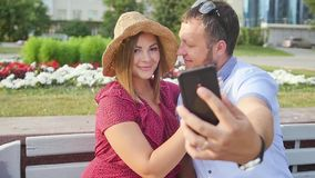 Young couple taking a selfie portrait while relaxing in a city park. Happy lovers want to capture a pleasant moment stock video