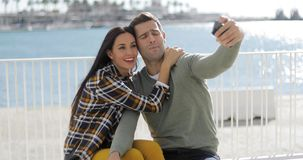 Young couple taking a selfie at the seaside stock video