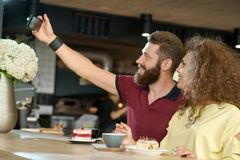 Young couple taking selfie sitting in fashionable cafe, drinking coffee. stock photos