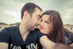 Young couple taking selfie with smartphone or camera at the beac. H Stock Photography