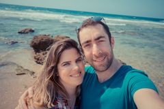 Young couple taking selfie with smartphone or camera at the beac. H Royalty Free Stock Photos