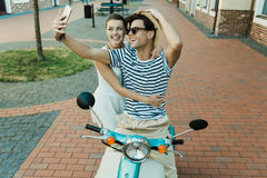 Young couple taking selfie on smartphone while sitting on scooter outdoors Royalty Free Stock Photography