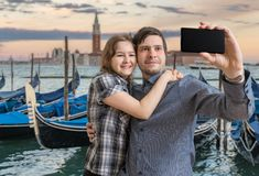 Young couple is taking selfie with smartphone in Venice in Italy. Gondolas in background royalty free stock images