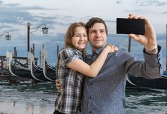 Young couple is taking selfie with smartphone in Venice in Italy. Gondolas in background royalty free stock photo