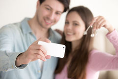 Young couple taking selfie using smartphone holding keys to apar. Happy smiling young couple showing keys of their new home and taking selfie picture to remember Royalty Free Stock Photo